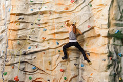 Woman climbing on man-made cliff Stock Images