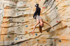 Woman climbing on man-made cliff Royalty Free Stock Photos