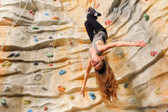 Woman climbing on man-made cliff Royalty Free Stock Image