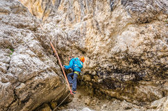 Woman climbing on metal ladder in via ferrata Stock Photo