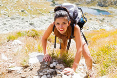 Woman Climbing Mountain. Woman enjoying climbing up a rocky mountain with big backpack Stock Images