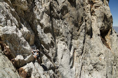Woman Climbing Mountain. Woman climbing up a steep mountain face without a rope Royalty Free Stock Photography