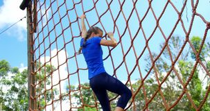 Woman climbing a net during obstacle course 4k. Woman climbing a net during obstacle course in boot camp 4k stock video