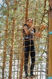 Woman climbing a net during obstacle course. Tyumen royalty free stock image