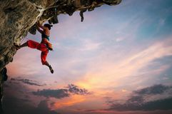 Athletic Woman climbing on overhanging cliff rock with sunset sky background royalty free stock images