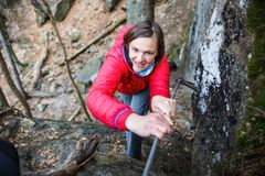 Woman climbing rock, holding security railing Royalty Free Stock Images