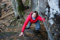 Woman climbing rock, holding security railing Royalty Free Stock Photo