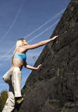 Woman climbing rock wall. Royalty Free Stock Photos