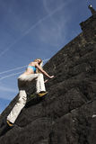 Woman climbing rock wall. Stock Image