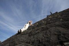 Woman climbing rock wall. Stock Photos