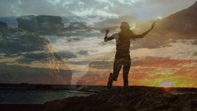 Woman climbing rocks beside ocean. Silhouette of a woman climbing rocks beside ocean with a view of the sunset stock footage