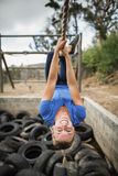 Woman climbing rope during obstacle course training stock image