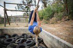 Woman climbing rope during obstacle course training royalty free stock image