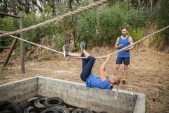 Woman climbing rope during obstacle course training stock photography