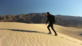 Woman climbing a sand dune. In the death valley stock video