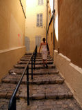 Woman climbing stairs. Woman with a white dress is climbing old stoned stairs royalty free stock photography