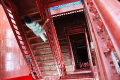 Woman climbing the stairs. Woman in blue sand white striped dress climbing the stairs of high rise apartment block the woodwork  giving a red cast to the Stock Photos