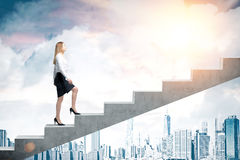 Woman climbing stairs in city. Side view of a woman wearing a black skirt and a white blouse and climbing stairs. There is a city panorama in the background and Royalty Free Stock Photos