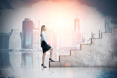 Woman climbing stairs and cityscape at dawn. Woman climbing stairs against cityscape with skyscrapers. Concept of career ladder. Mock up. Toned image Royalty Free Stock Image