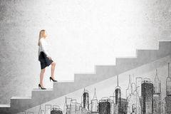 Woman climbing stairs, concrete wall. Side view of a woman wearing a black skirt and a white blouse and climbing stairs. There is a city sketch on a concrete Royalty Free Stock Images