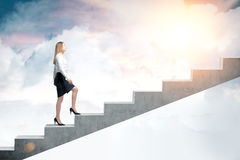 Woman climbing to the sky. Side view of a blond woman in a black skirt and a white blouse and climbing stairs to the sky. Concept of a road to success in Royalty Free Stock Photo