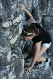 Woman climbing up a mountain Stock Photo