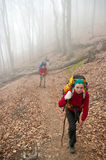 A woman climbing up the mountain ahead the group Royalty Free Stock Photos