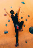 Woman climbing up on practice wall indoors Stock Image