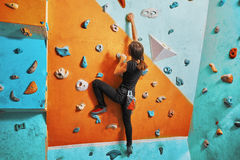 Woman climbing up on practice wall Royalty Free Stock Images