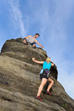 Woman climbing up rock man hold rope Royalty Free Stock Image