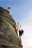 Woman climbing up rock man hold rope Royalty Free Stock Photo