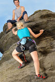 Woman climbing up rock man hold rope Stock Images