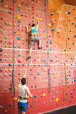 Woman climbing up rock wall Stock Photography