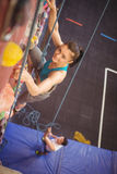 Woman climbing up rock wall Stock Photo