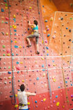 Woman climbing up rock wall Royalty Free Stock Image
