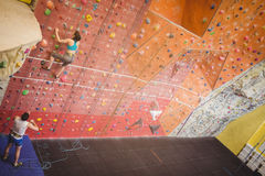 Woman climbing up rock wall Royalty Free Stock Photography
