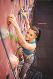 Woman climbing up rock wall Stock Photos