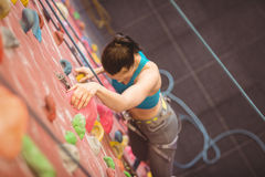Woman climbing up rock wall Stock Images