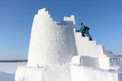 Woman climbing up the steps of a snow tower, Novosibirsk, Russia. Woman climbing up the steps of snow tower, Novosibirsk, Russia royalty free stock images