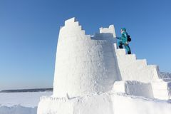 Woman climbing up the steps of a snow tower, Novosibirsk, Russia. Woman climbing up the steps of snow tower, Novosibirsk, Russia royalty free stock photography