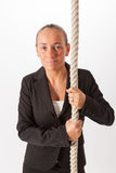 The woman is climbing up a thick rope Stock Image