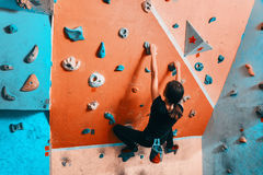 Woman climbing up on wall indoors Royalty Free Stock Photos