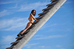 Woman climbing up a wooden ladder Stock Photo
