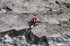 Woman climbing a vertical rock along river Meuse in Belgium Royalty Free Stock Images