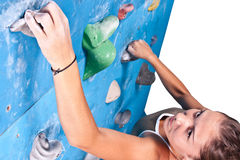 Woman on climbing wall. Athletic girl climbing on an indoor rock-climbing wall Stock Photography
