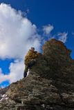 A woman climbs a cliff. Stock Image