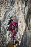 Woman climbs a rock. With rope, lead Stock Photo