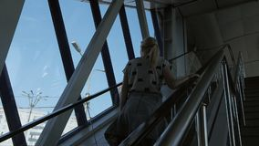 A woman climbs up the escalator in a business center or airport. A woman with long blonde hair climbs up the escalator at a business center or airport stock footage