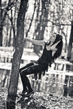 Woman clings to a tree. Black and white photo. Cute woman clings to a tree. Black and white photo Royalty Free Stock Photo