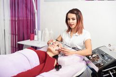 Woman at clinic receiving stimulating electric facial treatment from therapist. Beautiful women at spa clinic receiving stimulating electric facial treatment Royalty Free Stock Photography